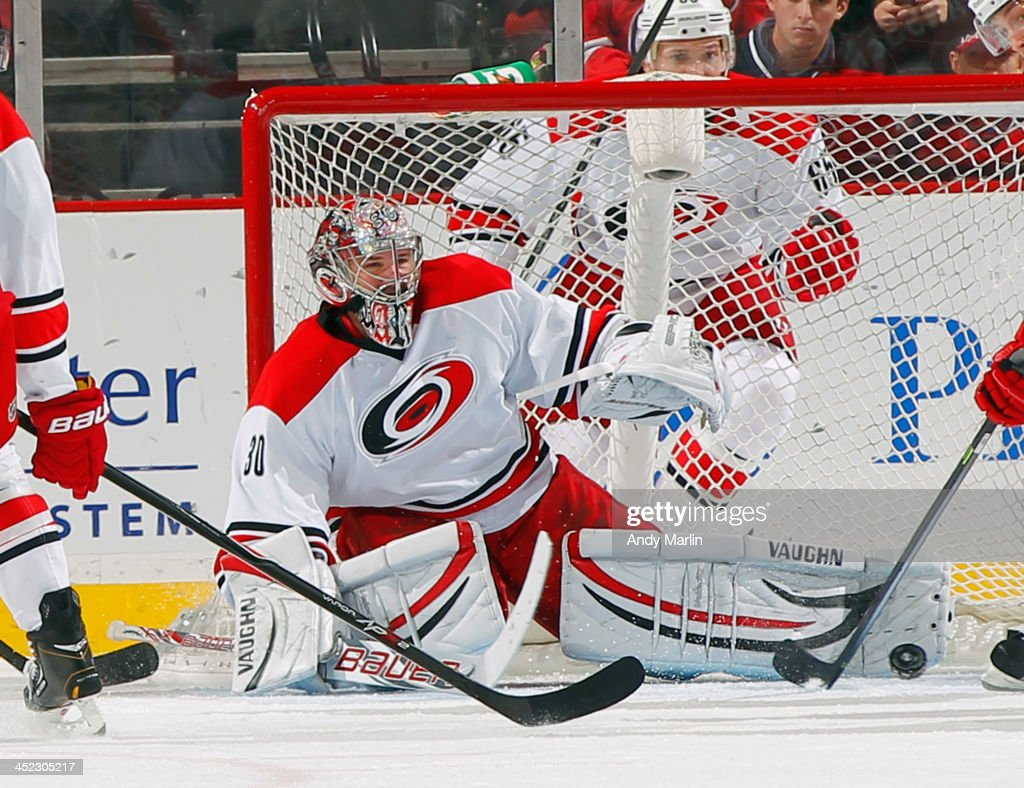 Cam Ward #30 of the Carolina Hurricanes makes a pad save against the New Jersey Devils during the game at the Prudential Center on November 27, 2013 in Newark, New Jersey.