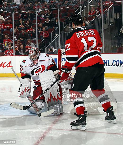 Cam Ward of the Carolina Hurricanes makes a pad save as Brian Rolston of the New Jersey Devils looks for a rebound at the Prudential Center on...