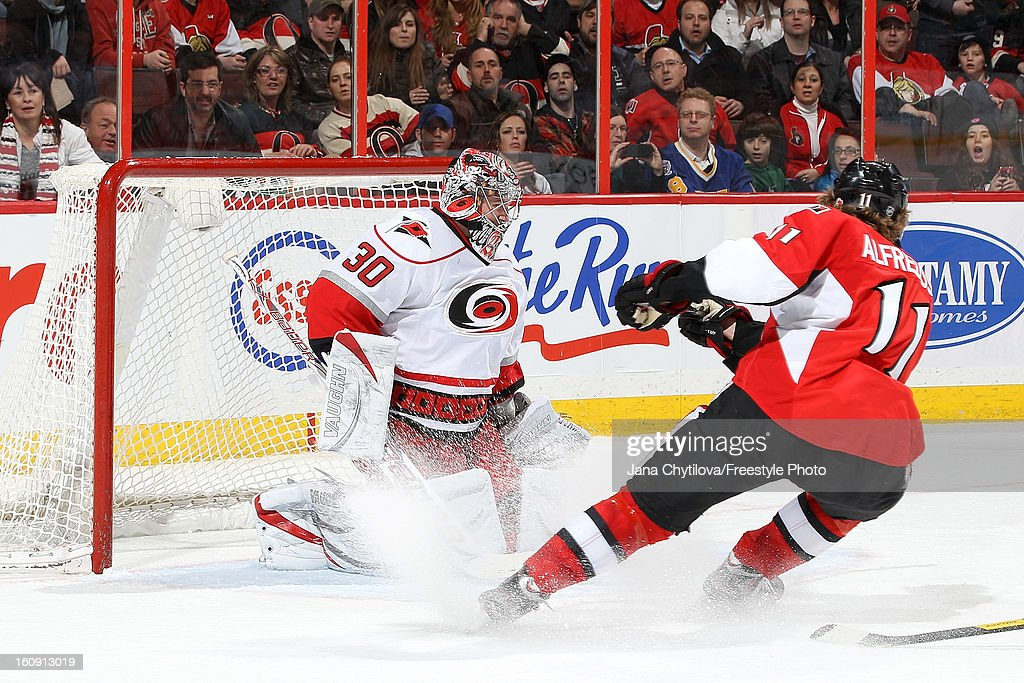 Cam Ward #30 of the Carolina Hurricanes makes a save against Daniel Alfredsson #11 of the Ottawa Senators, during an NHL game at Scotiabank Place on February 7, 2013 in Ottawa, Ontario, Canada.