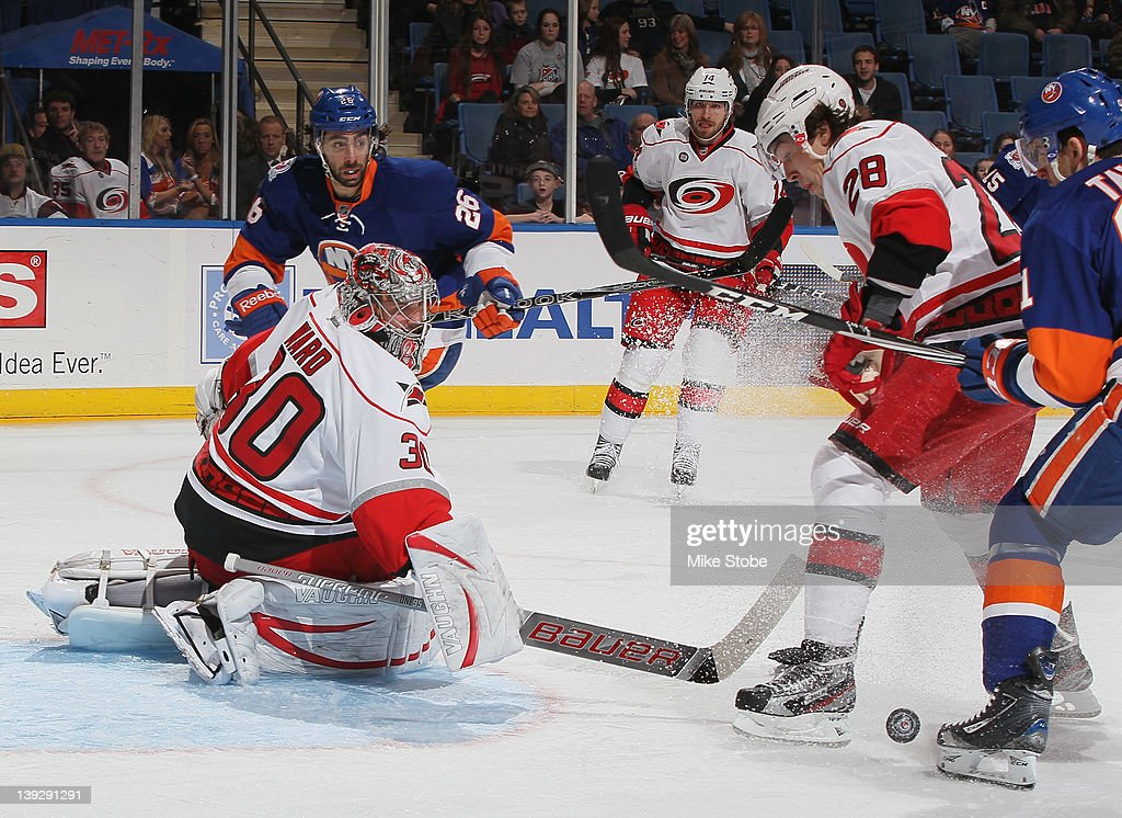 <a gi-track='captionPersonalityLinkClicked' href=/galleries/search?phrase=Cam+Ward&family=editorial&specificpeople=453216 ng-click='$event.stopPropagation()'>Cam Ward</a> #30 of the Carolina Hurricanes makes a save as teammate Justin Faulk #28 and <a gi-track='captionPersonalityLinkClicked' href=/galleries/search?phrase=John+Tavares&family=editorial&specificpeople=601791 ng-click='$event.stopPropagation()'>John Tavares</a> #91 of the New York Islanders look for the rebound at Nassau Veterans Memorial Coliseum on February 18, 2012 in Uniondale, New York. The Islanders defeated the Hurricanes 4-3.
