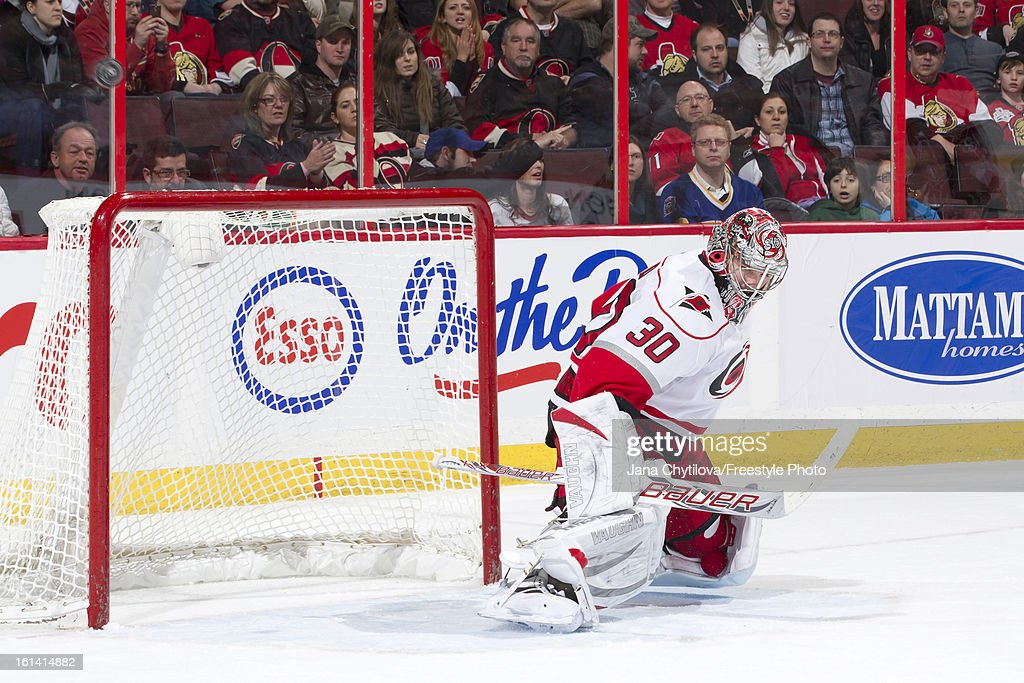Cam Ward #30 of the Carolina Hurricanes makes a save as the puck goes over the net, during an NHL game against the Ottawa Senators at Scotiabank Place on February 7, 2013 in Ottawa, Ontario, Canada.