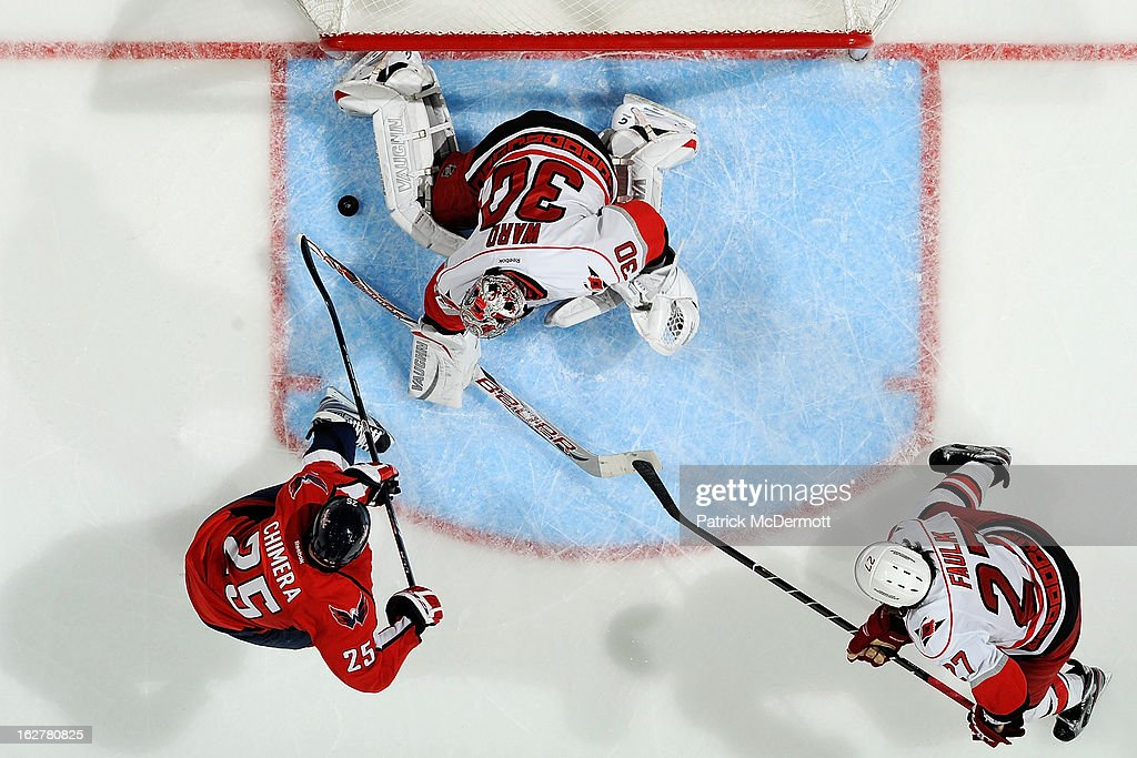 <a gi-track='captionPersonalityLinkClicked' href=/galleries/search?phrase=Cam+Ward&family=editorial&specificpeople=453216 ng-click='$event.stopPropagation()'>Cam Ward</a> #30 of the Carolina Hurricanes makes a save on <a gi-track='captionPersonalityLinkClicked' href=/galleries/search?phrase=Jason+Chimera&family=editorial&specificpeople=211264 ng-click='$event.stopPropagation()'>Jason Chimera</a> #25 of the Washington Capitals during an NHL game at Verizon Center on February 26, 2013 in Washington, DC.