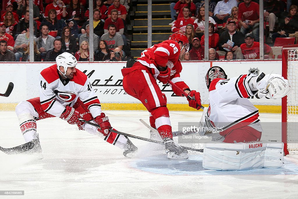 <a gi-track='captionPersonalityLinkClicked' href=/galleries/search?phrase=Cam+Ward&family=editorial&specificpeople=453216 ng-click='$event.stopPropagation()'>Cam Ward</a> #30 of the Carolina Hurricanes makes a save on Tomas Jurco #26 of the Detroit Red Wings as teammate <a gi-track='captionPersonalityLinkClicked' href=/galleries/search?phrase=Jay+Harrison&family=editorial&specificpeople=714374 ng-click='$event.stopPropagation()'>Jay Harrison</a> #44 helps from behind during an NHL game on April 11, 2014 at Joe Louis Arena in Detroit, Michigan.