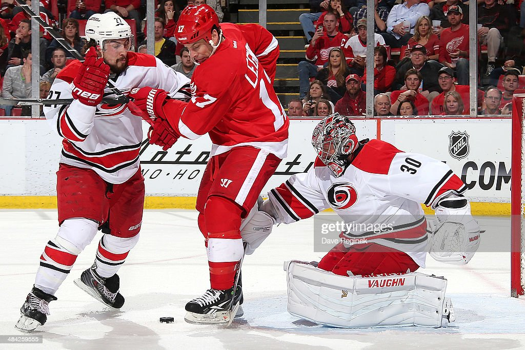 <a gi-track='captionPersonalityLinkClicked' href=/galleries/search?phrase=Cam+Ward&family=editorial&specificpeople=453216 ng-click='$event.stopPropagation()'>Cam Ward</a> #30 of the Carolina Hurricanes makes a save with <a gi-track='captionPersonalityLinkClicked' href=/galleries/search?phrase=David+Legwand&family=editorial&specificpeople=202553 ng-click='$event.stopPropagation()'>David Legwand</a> #17 of the Detroit Red Wings and teammate Justin Faulk #27 battling in front of him during an NHL game on April 11, 2014 at Joe Louis Arena in Detroit, Michigan.