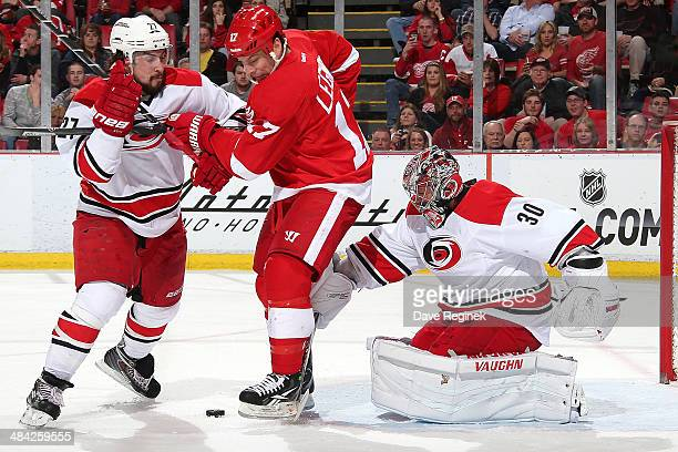 Cam Ward of the Carolina Hurricanes makes a save with David Legwand of the Detroit Red Wings and teammate Justin Faulk battling in front of him...