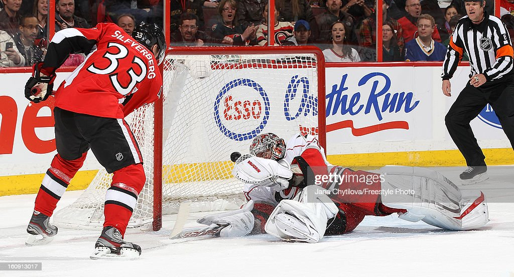 Cam Ward #30 of the Carolina Hurricanes makes a trapper save against Jakob Silfverberg #33 of the Ottawa Senators during an NHL game at Scotiabank Place on February 7, 2013 in Ottawa, Ontario, Canada.