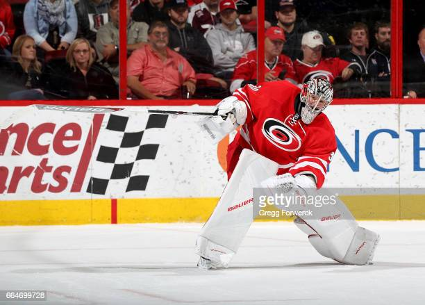 Cam Ward of the Carolina Hurricanes passes the puck during an NHL game against the Detroit Red Wings on March 28 2017 at PNC Arena in Raleigh North...