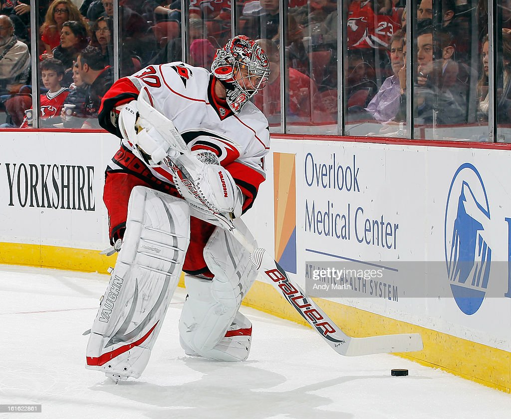 Cam Ward #30 of the Carolina Hurricanes plays the puck against the New Jersey Devils during the game at the Prudential Center on February 12, 2013 in Newark, New Jersey.