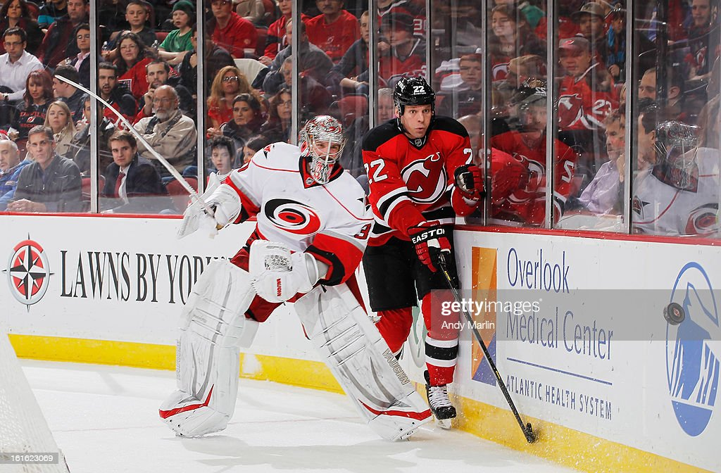 Cam Ward #30 of the Carolina Hurricanes plays the puck away from Krystofer Barch #22 of the New Jersey Devils during the game at the Prudential Center on February 12, 2013 in Newark, New Jersey.
