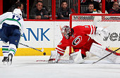 Cam Ward of the Carolina Hurricanes reaches out to block a scoring attempt by Radim Vrbata of the Vancouver Canucks during their NHL game at PNC...