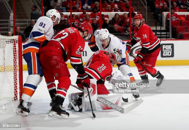 Cam Ward of the Carolina Hurricanes smothers the puck as teammate Brett Pesce defends and Anders Lee of the New York Islanders tries to chip it past...