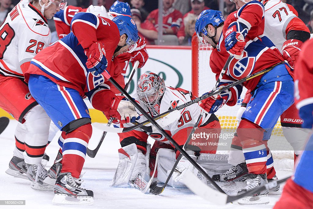 Cam Ward #30 of the Carolina Hurricanes stops the puck in front of Francis Bouillon #55 and Brian Gionta #21 of the Montreal Canadiens during the NHL game at the Bell Centre on February 18, 2013 in Montreal, Quebec, Canada.