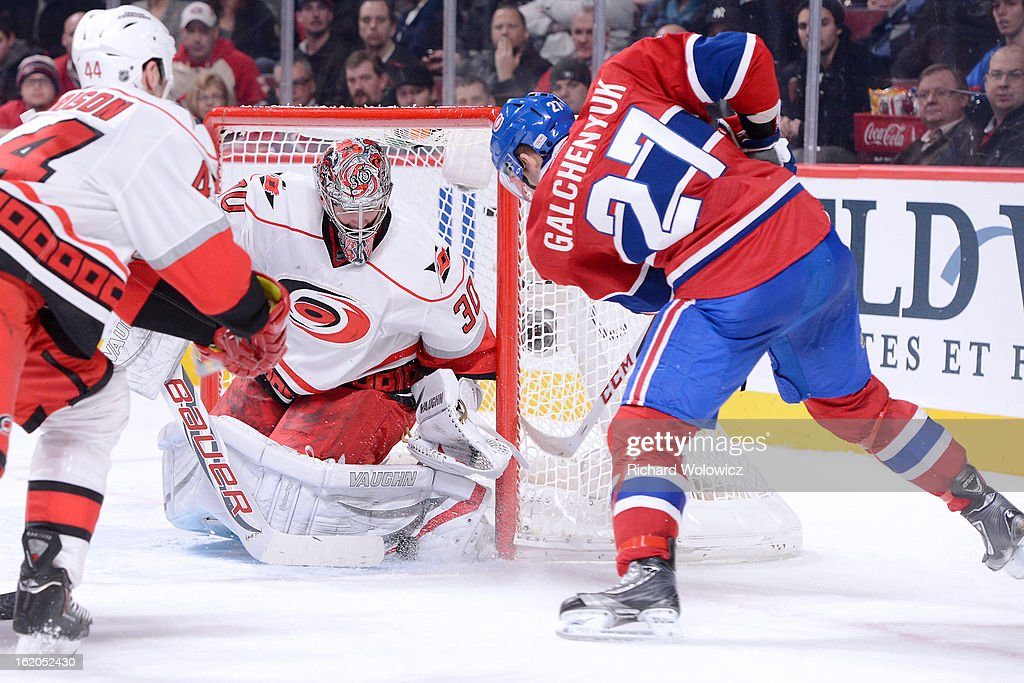 Cam Ward #30 of the Carolina Hurricanes stops the puck on an attempt by Alex Galchenyuk #27 of the Montreal Canadiens during the NHL game at the Bell Centre on February 18, 2013 in Montreal, Quebec, Canada.