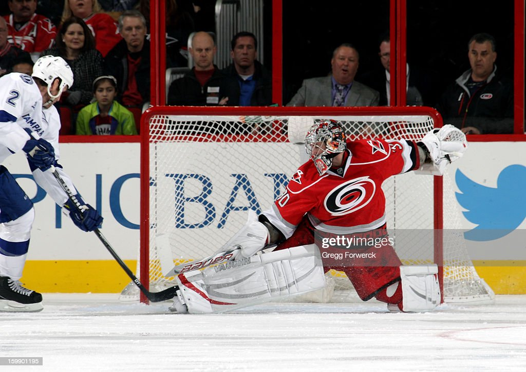 Cam Ward #30 of the Carolina Hurricanes stretches out to make a save as Eric Brewer #2 of the Tampa Bay Lightning attempt to collect the puck during an NHL game on January 22, 2013 at PNC Arena in Raleigh, North Carolina.