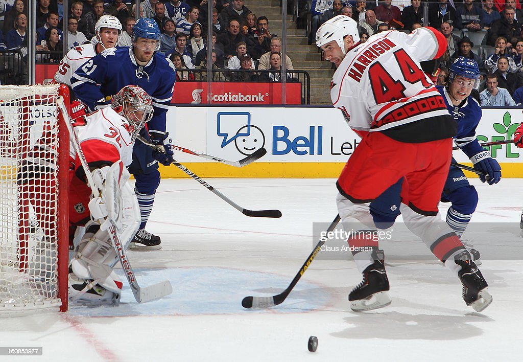 Cam Ward #30 of the Carolina Hurricanes watches a puck roll away from teammate Jay Harrison #44 in a game against the Toronto Maple Leafs on February 4, 2013 at the Air Canada Centre in Toronto, Canada. The Hurricanes defeated the Leafs 4-1.