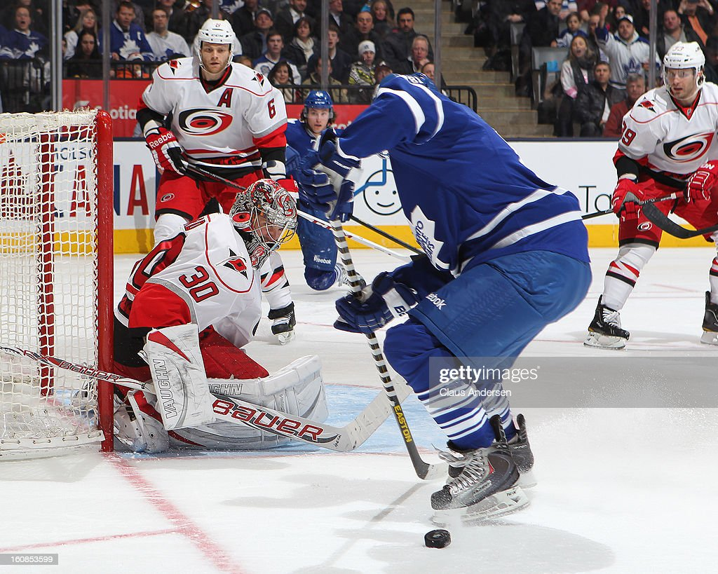 Cam Ward #30 of the Carolina Hurricanes watches as a scoring attempt by Phil Kessel #81 of the Toronto Maple Leafs is stopped in a game on February 4, 2013 at the Air Canada Centre in Toronto, Canada. The Hurricanes defeated the Leafs 4-1.
