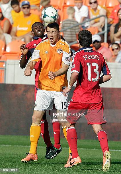 Cam Weaver of the Houston Dynamo heads the ball away from Patrick Nyarko of the Chicago Fire as /c13 looks on at BBVA Compass Stadium on April 14...
