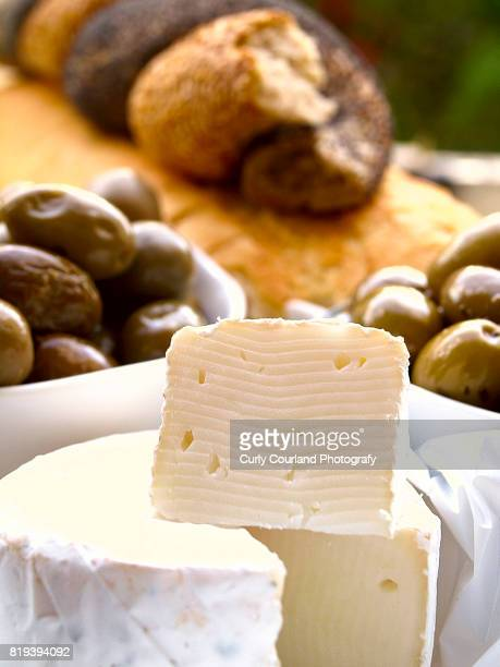 Camambert cheese served with olives and bread with sesame seeds and poppy seeds