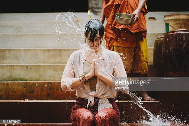 Cambodia, Buddhist monk water blessing young woman