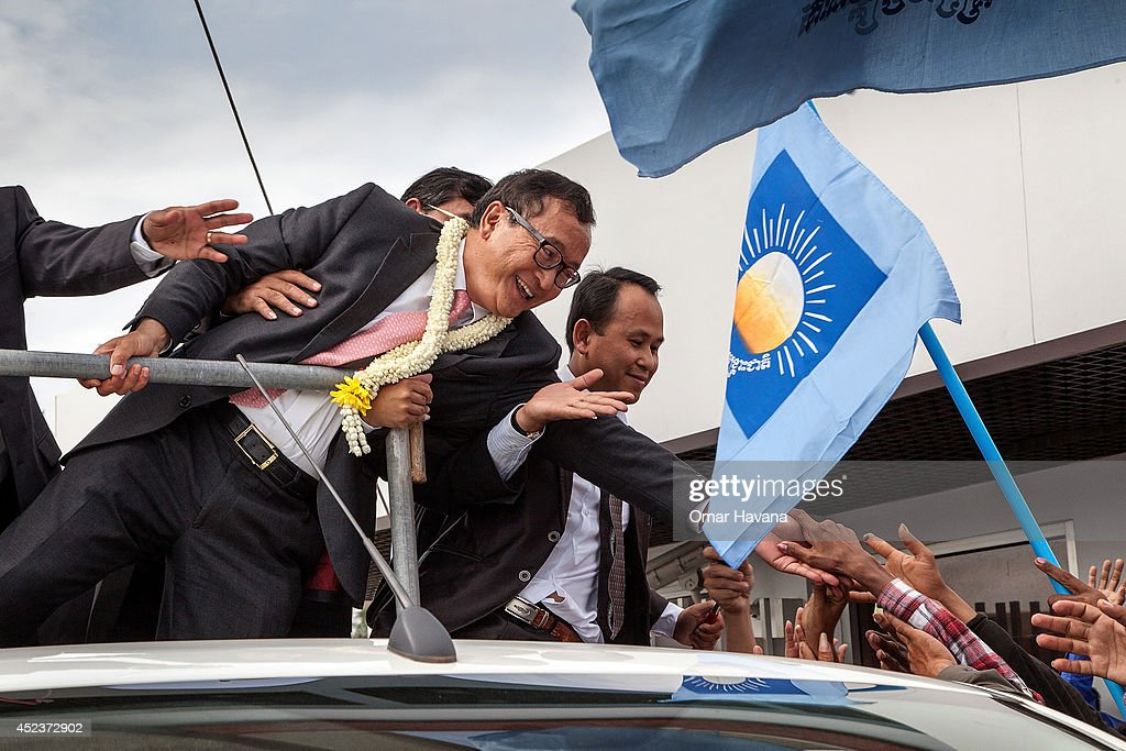 Cambodia National Rescue Party President Sam Rainsy greets supporters at Phnom Penh International Airport after arriving in Cambodia on July 19 2014...