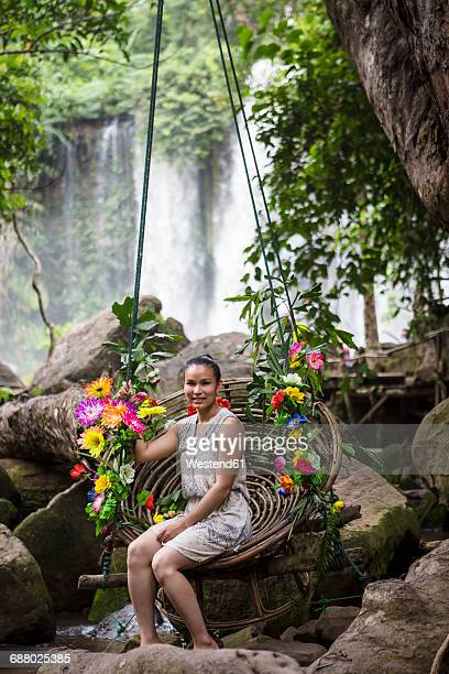 Cambodia, Nationalpark Phnom Kulen, young woman sitting on swing in front of waterfalls