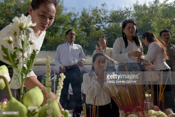 Cambodia people pray in front of skulls at the Choeung Ek killing fields memorial in Phnom Penh on May 18 2017 More than 1000 people watched...
