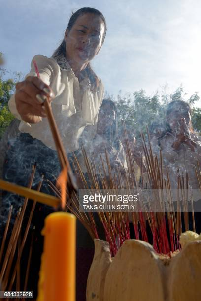 A Cambodia woman burns incense sticks as she prays at the Choeung Ek killing fields memorial in Phnom Penh on May 18 2017 More than 1000 people...