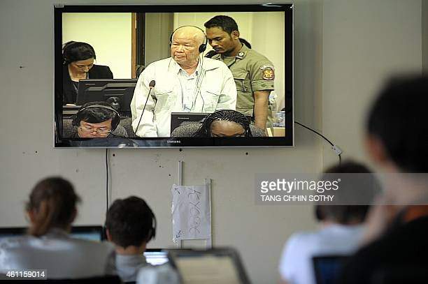 Cambodian and international journalists watch a live video feed showing former Khmer Rouge leader head of state Khieu Samphan during a hearing for...