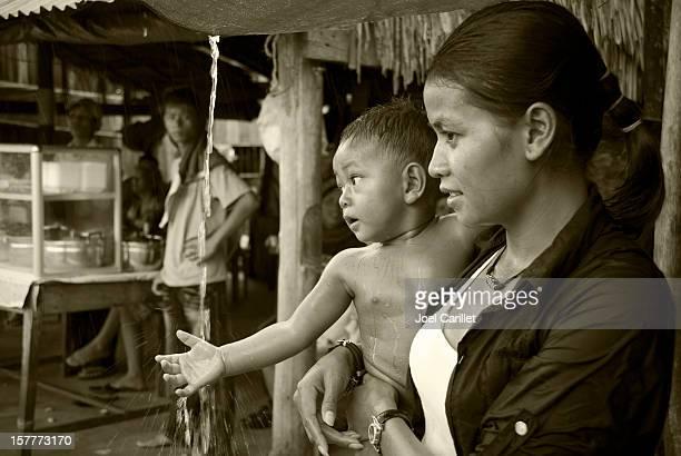 Cambodian baby touching falling water