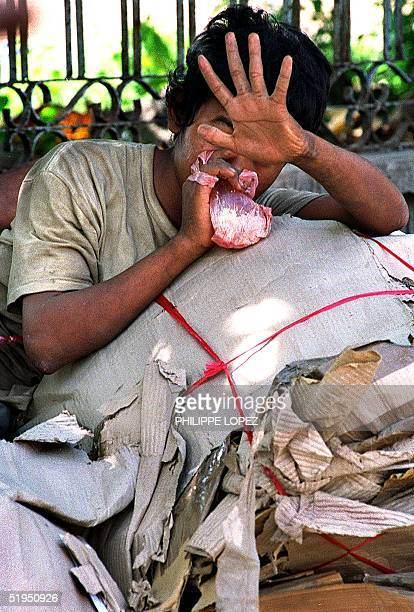 Cambodian boy standing over a rubbish pile hides his face as sniffs glue from a plastic bag in Phnom Penh 18 December 2000 Social workers say glue is...