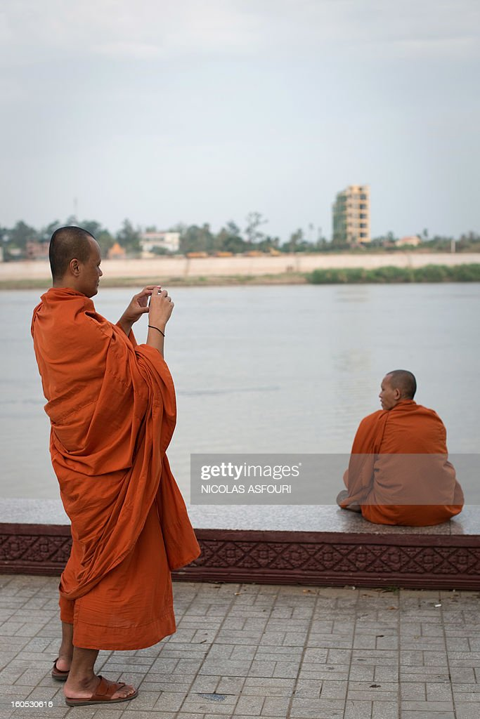 A Cambodian Buddhist monk takes a photograph near the Royal Palace in Phnom Penh on February 2, 2013. A sea of mourners filled the streets of the Cambodian capital on February 1, for a lavish funeral for revered former king Norodom Sihanouk, who towered over six tumultuous decades in his nation's history. AFP PHOTO/ Nicolas ASFOURI