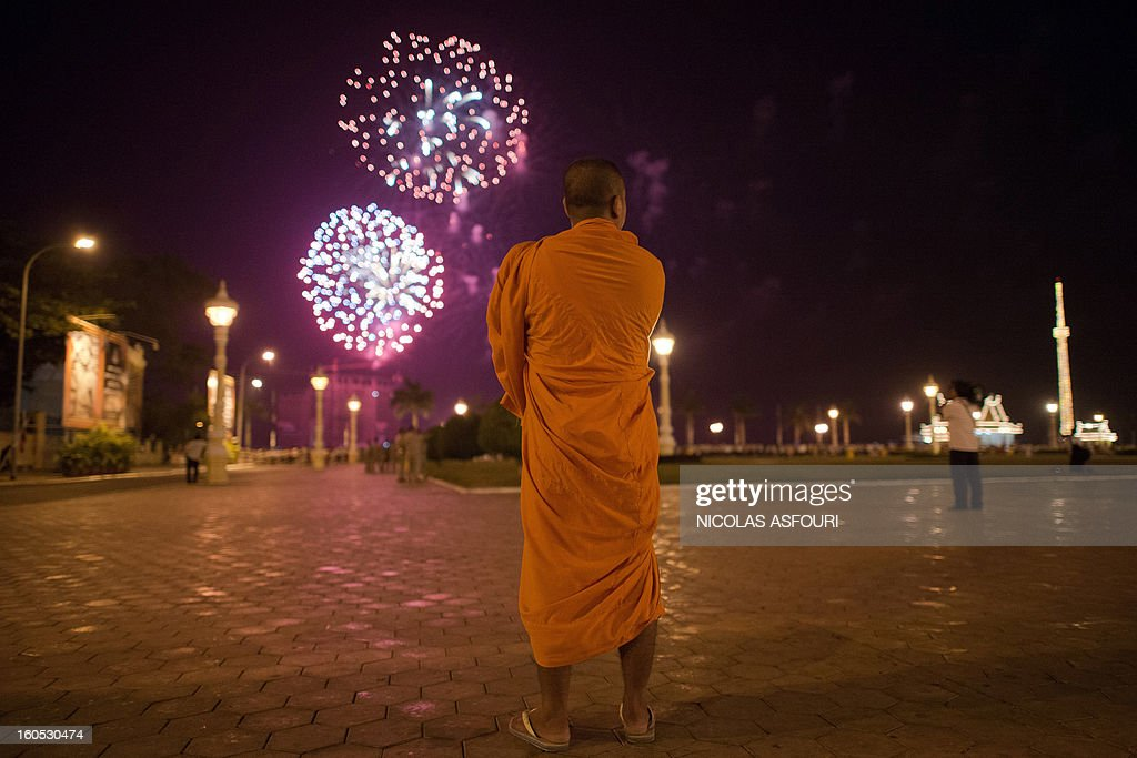 A Cambodian Buddhist monk watches fireworks from the Royal Palace in Phnom Penh on February 2, 2013. A sea of mourners filled the streets of the Cambodian capital on February 1, for a lavish funeral for revered former king Norodom Sihanouk, who towered over six tumultuous decades in his nation's history. AFP PHOTO/ Nicolas ASFOURI