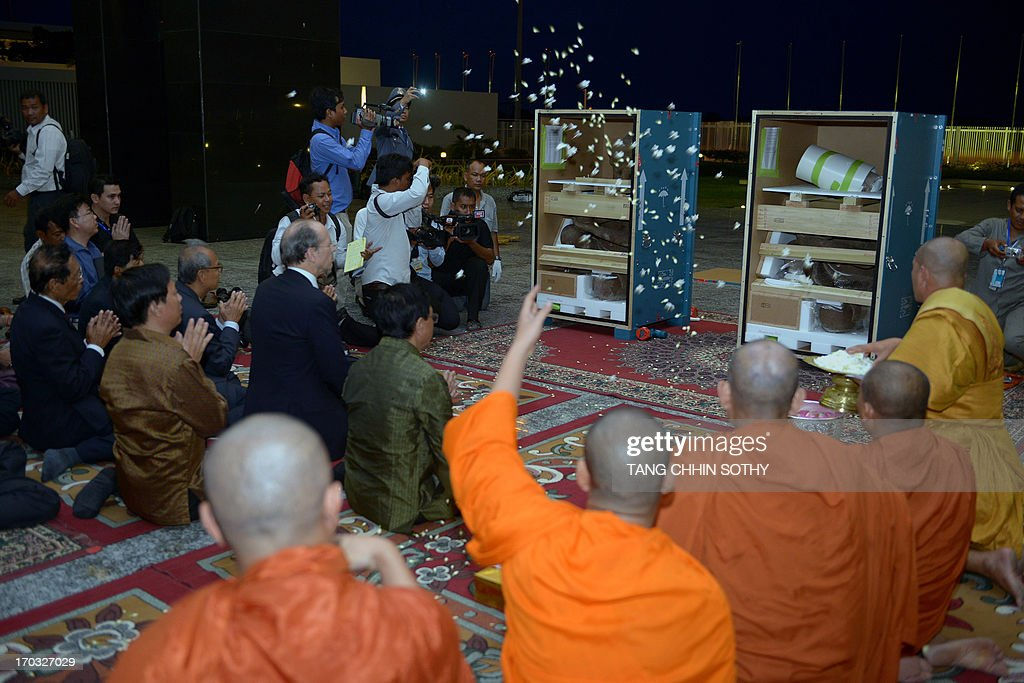 Cambodian Buddhist monks bless flowers for two 10th century statues upon their arrival at Phnom Penh International Airport on June 11, 2013. Two statues that Cambodia says were looted from a jungle temple several decades ago were returned home on June 11 from New York's Metropolitan Museum of Art, in what the kingdom described as a 'historic' moment. AFP PHOTO/ TANG CHHIN SOTHY