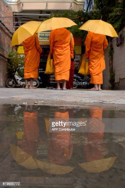 Cambodian Buddhist monks collect alms along a street in Phnom Penh on July 21 2017 / AFP PHOTO / TANG CHHIN SOTHY