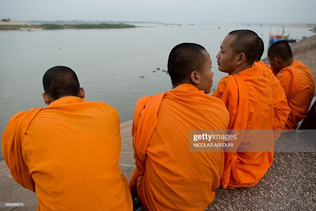 Cambodian Buddhist monks look out onto the Mekong river as people come to pray and pay their respects for the late former king Norodom Sihanouk in front the Royal Palace in Phnom Penh on February 3, 2013. Thousands of Cambodians have paid their last respects to their beloved former king Norodom Sihanouk as his body lay in state ahead of his cremation on February 4. AFP PHOTO/ Nicolas ASFOURI