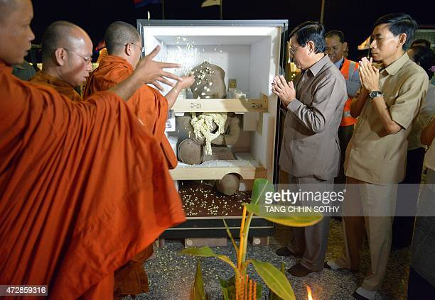 Cambodian Buddhist monks scatter flowers over a 10th century statue upon its arrival at Phnom Penh International Airport on May 10 2015 A statue that...