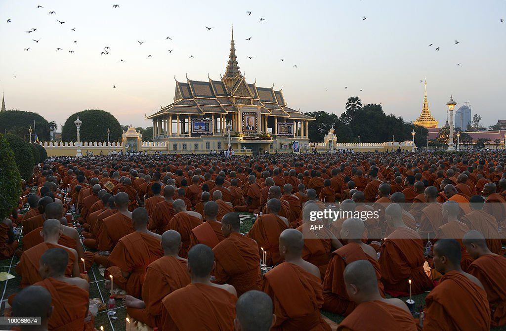 Cambodian Buddhist monks sit during a prayer ceremony in front of the Royal Palace in Phnom Penh on January 26, 2013. Tens of thousands of Cambodian Buddhist monks and people gathered to pray for the late former King Norodom Sihanouk. Cambodia's beloved former monarch Norodom Sihanouk, who died aged 89, will be cremated on February 4 following an elaborate ceremony, Cambodian Prime Minister Hun Sen said on November 26, 2012.