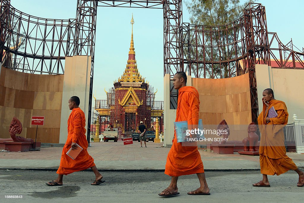 Cambodian Buddhist monks walk past a construction site being prepared for the forthcoming cremation ceremony of the late former King Norodom Sihanouk, near the Royal Palace in Phnom Penh on January 3, 2013. Cambodia's beloved former monarch Norodom Sihanouk, who died aged 89 last month, will be cremated on February 4 following an elaborate ceremony, Cambodian Prime Minister Hun Sen said on November 26, 2012.