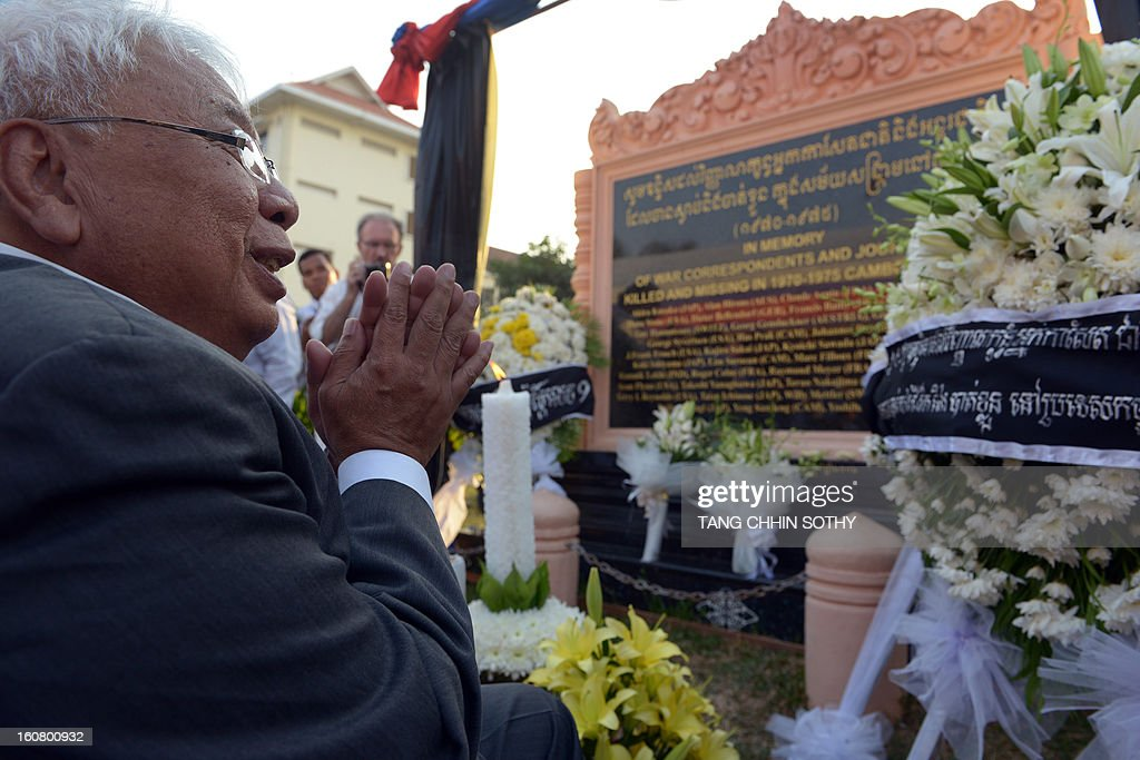 Cambodian Chhang Song (L), former information minister, prays in front of a memorial sign (back C) at a park in front of the Le Royal hotel on February 6, 2013. Cambodia on February 6 officially unveiled a memorial to dozens of foreign and local journalists killed covering the country's 1970-75 war won by the communist Khmer Rouge regime. Led by 'Brother Number One' Pol Pot, who died in 1998, the Khmer Rouge wiped out nearly a quarter of the population through starvation, overwork or execution during its 1975-1979 rule in a bid to forge a communist utopia.