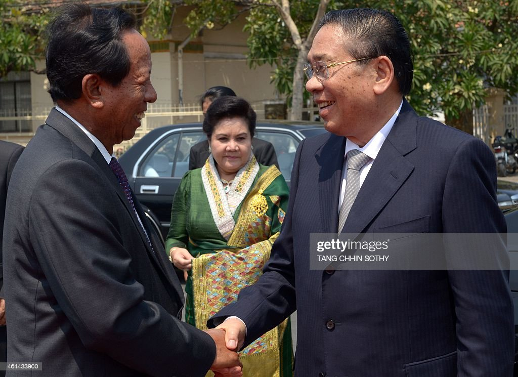Cambodian Defence Minister Tea Banh (L) shakes hands with Laos President <a gi-track='captionPersonalityLinkClicked' href=/galleries/search?phrase=Choummaly+Sayasone&family=editorial&specificpeople=556173 ng-click='$event.stopPropagation()'>Choummaly Sayasone</a> (R), as the latter's wife Keosaychay Sayasone (C) looks on, during a visit to the Independence Monument in Phnom Penh on February 26, 2015. Choummaly arrived here for a two-day official visit.