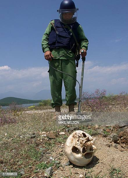 Cambodian deminer checks the area around a skull 23 July 1999 during an operation to clear a popular swimming area of cluster bombs dropped on Serb...