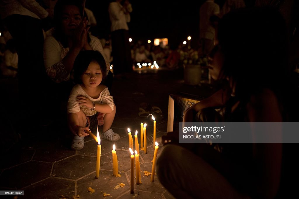 A Cambodian girl (centre L) lights candles for the late former King Norodom Sihanouk in front of the Royal Palace in Phnom Penh on January 31, 2013 ahead of a lavish funeral procession on February 1 which will see his body carried from the royal palace in Phnom Penh to a funeral pyre in a nearby park and is expected to draw more than one million mourners to the capital's streets. Sihanouk, who abdicated in 2004 after steering Cambodia through six decades marked by independence from France, civil war, the murderous Khmer Rouge regime and finally peace, died of a heart attack in Beijing on October 15, 2012 and will be cremated on February 4. AFP PHOTO/ Nicolas ASFOURI