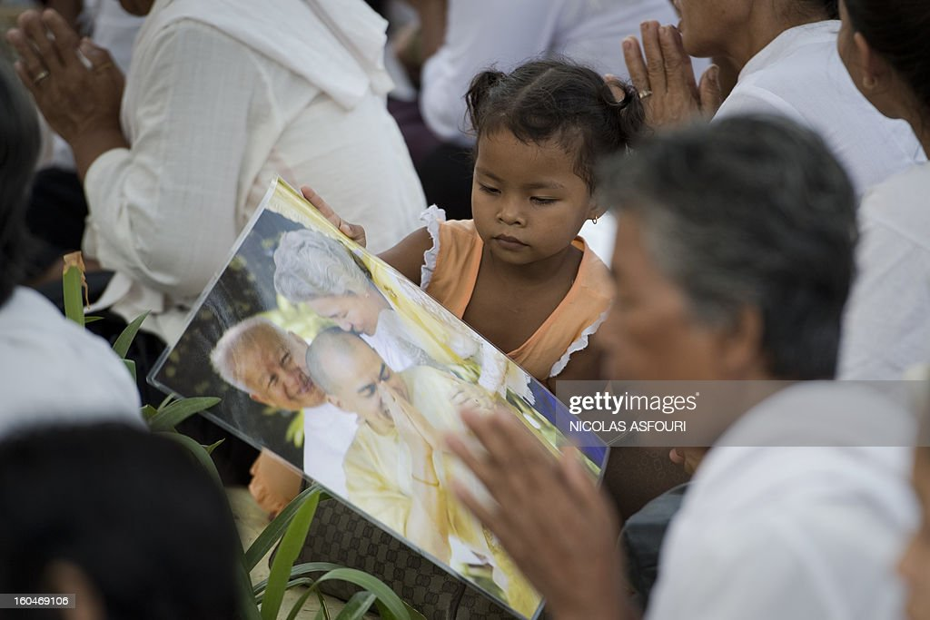 A Cambodian girl (C) looks at a photograph of the late former King Norodom Sihanouk together with Sihanouk's widow Queen Monique (R, in the photograph) and King Norodom Sihamoni (C, in the photograph) in front of the Royal Palace in Phnom Penh on February 1, 2013 as a sea of mourners filled the streets of the Cambodian capital for a lavish funeral for the revered former king. Sihanouk, who abdicated in 2004 after steering Cambodia through six decades marked by independence from France, civil war, the murderous Khmer Rouge regime and finally peace, died of a heart attack in Beijing on October 15, 2012 and will be cremated on February 4. AFP PHOTO / Nicolas ASFOURI