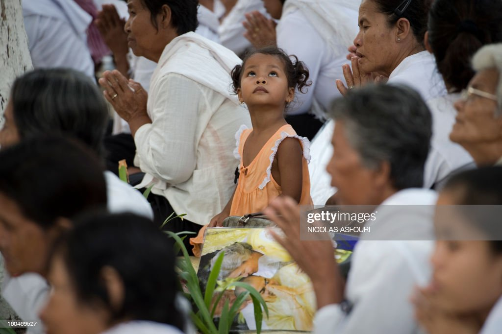 A Cambodian girl (C) looks up as she sits next to a photograph (bottom C) of the late former King Norodom Sihanouk together with Sihanouk's widow Queen Monique (R, in the photograph) and King Norodom Sihamoni (C, in the photograph) in front of the Royal Palace in Phnom Penh on February 1, 2013 as a sea of mourners filled the streets of the Cambodian capital for a lavish funeral for the revered former king. Sihanouk, who abdicated in 2004 after steering Cambodia through six decades marked by independence from France, civil war, the murderous Khmer Rouge regime and finally peace, died of a heart attack in Beijing on October 15, 2012 and will be cremated on February 4. AFP PHOTO / Nicolas ASFOURI