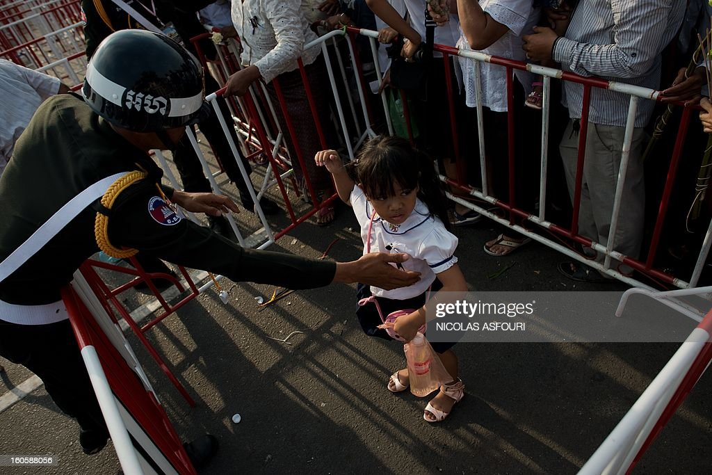 A Cambodian girl, placed by her parents behind a barrier is taken by a police officer as Cambodian people try to make their way through gates as they come to pray and pay their respect for the late former king Norodom Sihanouk near the Royal Palace in Phnom Penh on February 3, 2013. Thousands of Cambodians have paid their last respects to their beloved former king Norodom Sihanouk as his body lay in state ahead of his cremation on February 4. AFP PHOTO/ Nicolas ASFOURI