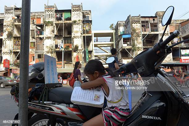 A Cambodian girl reads a book on a motorbike along a street in Phnom Penh on February 24 2015 AFP PHOTO/ TANG CHHIN SOTHY