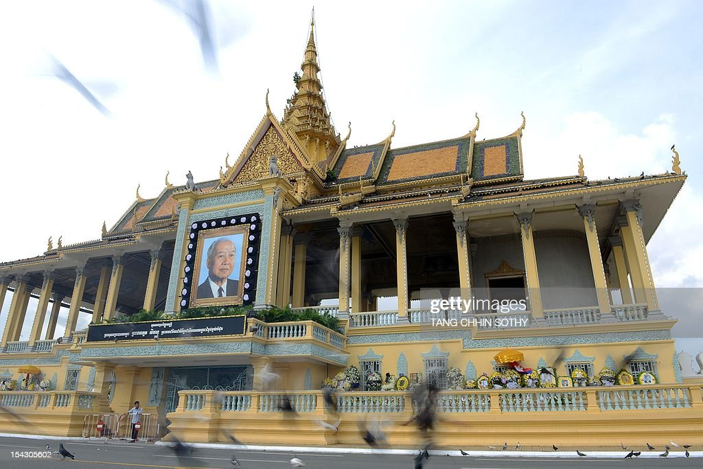 A Cambodian girl run as doves fly over the Royal Palace in Phnom Penh on October 18, 2012 after former king Norodom Sihanouk (pictured on portrait-L) died on October 15 at the age of 89. Experts in Cambodia began preparations on October 18 to embalm revered ex-king Norodom Sihanouk who will lie in state at the royal palace for three months ahead of a lavish funeral, a royal aide said.