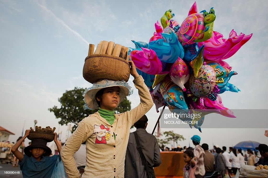 A Cambodian girl sell sweet sticky rice cooked in a bamboo called ''Khao Laam'' for people who come to pray and pay their respect for the late former king Norodom Sihanouk near the Royal Palace in Phnom Penh on February 3, 2013. Thousands of Cambodians have paid their last respects to their beloved former king Norodom Sihanouk as his body lay in state ahead of his cremation on February 4. AFP PHOTO/ Nicolas ASFOURI