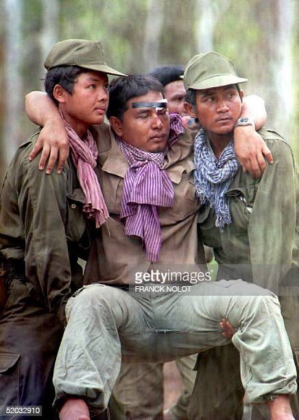 Cambodian government soldiers carry a wounded colleague 26 March 1994 outside Pailin the Khmer Rouge's former headquarters in western Cambodia...