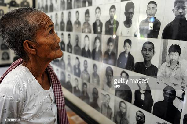 A Cambodian grandma looks at portrait photos of victims of the Khmer Rouge at the Tuol Sleng genocide museum in Phnom Penh on May 31 2011 Cambodia's...